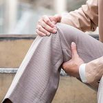 Elderly business man suffering from pain in knee at Office, closeup